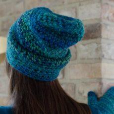 Długowłosa dziewczyna stoi tyłem w czapce i opiera się o mur dłonią w rękawiczce turkusowej