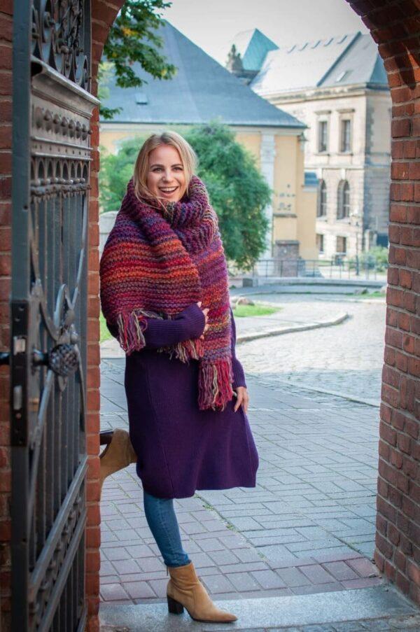 Piękna blondynka stoi przy bramie w dużym otulającym szalu w kolorach bordo, fiolet.