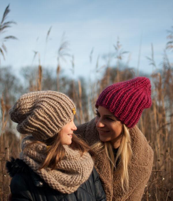 Dziewczyna i dziewczynka w zimowym ubraniu, w czapkach patrzą się na siebie, usmiechają się, za nimi sa suche trzciny