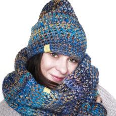 Ja w szarym swetrze pozuje w czapce, kominie i rekawiczka zrobionych na szydełku. kolor niebieskości z żółciami
