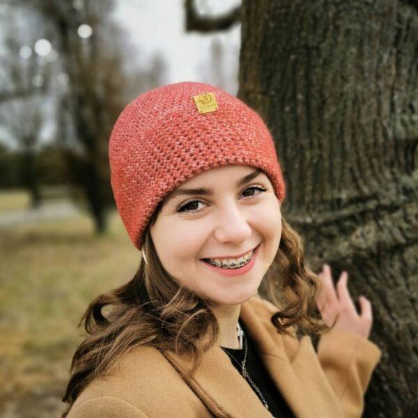 dziewczyna w czapce pieknie się usmiecha, ma aparat na zębach