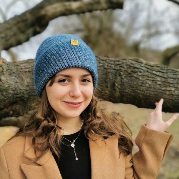 W parku. Dziewczyna na tle dzrzewa. W niebieskiej czapce i kamelowym płaszczu.