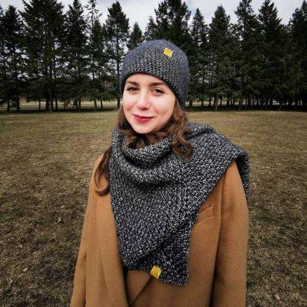 Na tle lasu stoi dziewczyna w czapce i chuście