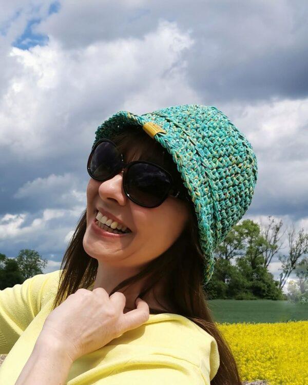 uśmiechnięta dziewczyna w zielonym dzierganym kapelutku
