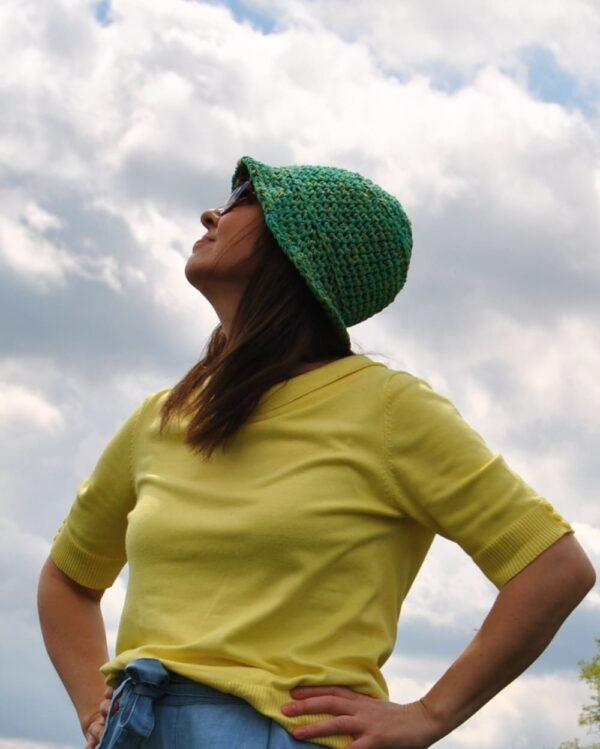 dziewczyna w kapelutku patrzy w niebio zachmurzone
