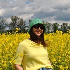 na tle pola rzepaku, dziewczyna w zielonym kapelutku