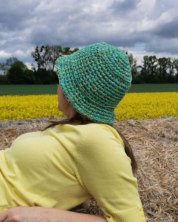na tle pola rzepaku dziewczyna w kapeluszu na szydełku